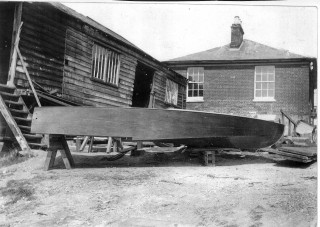 A hydroplane with stepped hull outside shed, an example of the company's versatility.  The Husk family home stands behind the shed.  Probably in the mid 1920s. | Nottage Maritime Institute 02048b