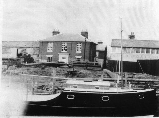 """A new Husk's cabin cruiser in front of James Husk's old house. This is typical of the more or less standard cabin cruiser. The house is now called """"The Old Customs House""""."""