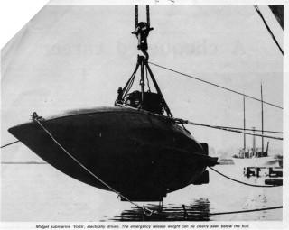 The Volta, here suspended from a crane, about to be lowered into the river.  In this picture her streamlined underwater shape can clearly be seen. | Nottage Maritime Institute 02086.17.4 Cropped