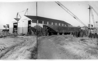 James W. Cook's big shed (the one that James Husk did not want to buy), with some lighters being built in the foreground.  These lighters are typical of the large number the firm built for their subsidiaries.  This picture was cropped from a panoramic view of the yard, hence the join in the middle. | Nottage Maritime Institute 02329g