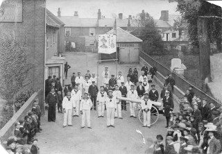 The parade to celebrate the Relief of Mafeking prepares to start from the Falcon Yard, next to St Mary's Church. The portraits of Lord Roberts and Baden Powell can be seen on the banner. | Nottage Maritime Institute 02416