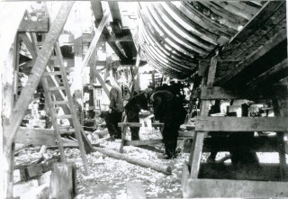 A motor minesweeper in frame with the first planks already in place. | Nottage Maritime Institute   02803