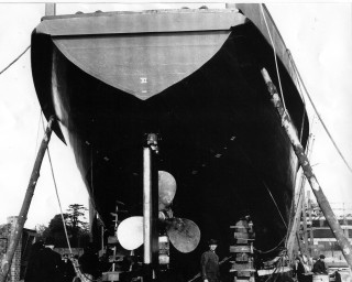 A 126 foot MMS ready to launch. Harold Sharman shipwright standing by the blocks.  Note the large propeller. | Nottage Maritime Institute 02820