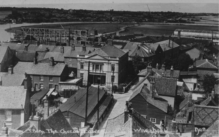 Looking out from St Mary's Church tower down West Street, the Forrestt shipyard  lies between the classical style building an the salt marshes.  The gantry beside the largest slipways is a very prominent feature.  The other side of the river is Rowhedge. | Nottage Maritime Institute 04332.4.001