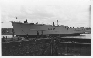 The newly launched H.M.S. Wiston is eased into the dry dock for fitting out.  She was the last of the three coastal minsweepers. | Nottage Maritime Institute 04501