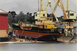 The 133grt self-propelled hopper dredger Kilmourne ready for launching, note the bunting.  She was launched without a ceremony on 24th July 1986 and completed a short time later by the liquidators for the Northern Ireland Harbour Authority, Belfast.  This was the last ship to be launched at Cook's.   | Nottage Maritime Institute, The Quay, Wivenhoe