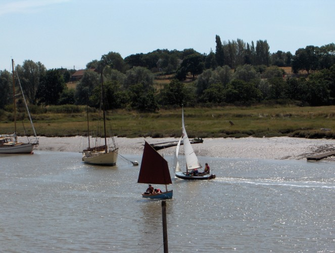 A Wivenhoe One Design sails past  a Nottage dinghy coming up river. | John Collins