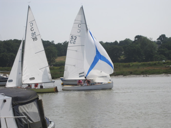 Brightlingsea One Design dinghies also compete.  Here a new boat, C53, coming up, passes an older boat sailing downriver.
