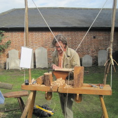 The wood turner with his traditional treadle lathe, demonstrates his craft.   John Collins