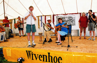 Wivenhoe Folk Club perform on stage with John Munday playing recorder, Jan Sinclair with the guitar (standing on the right are Joan Gifford and Alan van Loen waiting to perform)  | Sue Murray ARPS