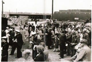 A gathering of people in Wivenhoe Shipyard for the launch of a ship in about 1943. Launches were social affairs, even in wartime.  Marion Husk is in this picture, centre right standing with one leg forward and hand to her face.         | Picture loaned by Barbara Husk