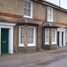 1-3 Clifton Terrace. A short brick terrace of three villas with substantial bay windows and intact door-cases. Gault brick (unusual for Wivenhoe) was used with a contrasting string course of red brickwork. A wall plaque states that these were built in 1887.   Photo by Joan Sawyer