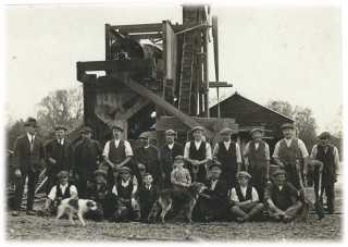 William G Loveless is standing on the left of this photograph. The young boy standing behind the Alsation dog is his son, Bill Loveless. The young man sitting to the left of the dog is Jack Glozier who worked in the office. Tony Forsgate's father, Tom Forsgate, who was foreman at the Pit for many years is standing in the back row next to Mr. Loveless. | Photograph loaned by Mr & Mrs Graham Wadley