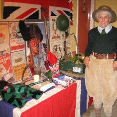 Phyllis Richardson wearing authentic Land Girl trousers, standing by a display in the Lobby of the William Loveless Hall. | Photo by Peter Hill