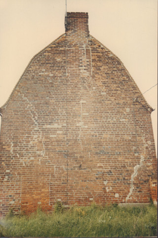 The gable end wall of the 'old workhouse' before it was rebuilt in 1983.  The major cracks in the wall were reputedly caused by the earthquake in 1884. You can also see the line of bricks indicating the line of the original roof before it was extended upwards. | Photo by Peter Hill