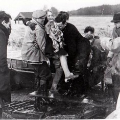 Mrs Woods of the Toll House, Ferry Road being helped into the rescue boat  by Mr Len Barton in the 1953 flood. | Wivenhoe Memories Collection