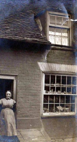Mrs Goodwin standing in the doorway of a shop in East Street. | Wivenhoe Memories