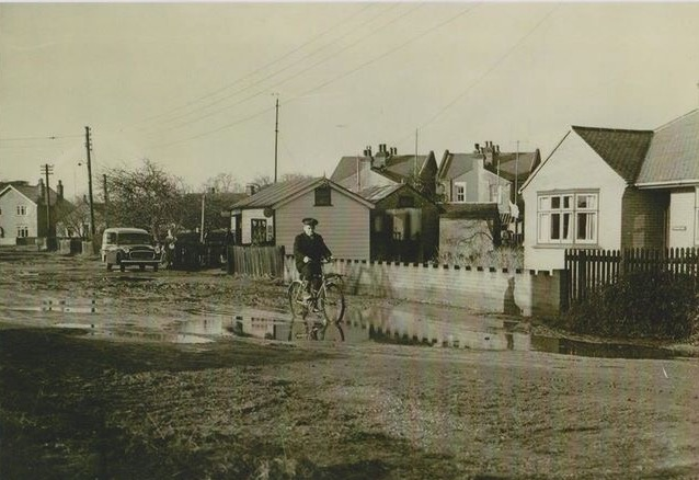 Sainty's shop in Stanley Road. The person on the bicycle  is local postman Jack Hatch cycling home after completing his morning post round. | Wivenhoe Memories Collection
