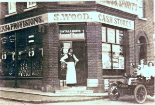 Stacey Wood's Grocery Store.  His assistant George Green is standing in the doorway. He married Nellie Pittuck and they had two children; Ivy who is seated at the wheel of the car and Ella with the ribbons in her hair.  Ella died in 1915 aged nine. | Wivenhoe Memories Collection
