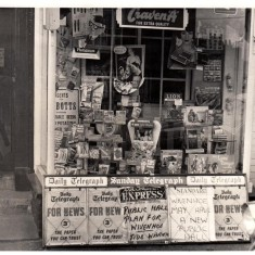 Jack Barrell on the doorstep of his paper shop in 1963. Note the newspaper headlines about the plan for a Public Hall.   Wivenhoe Memories Collection