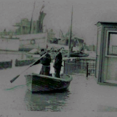 Wivenhoe Quay in 1953. Flooding outside Anchor House with two men in a dinghy | Photo from Helen Douzier
