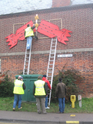 Putting up a decoration on the side of the old gatehouse building at Cedric's Garage - 2005     | Photo by Peter Hill