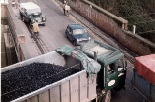Heavy lorries carrying coal from Wivenhoe Port in the1980s in the High Street and difficulties negotiating the junction by the railway bridge | Photo Mike Downes