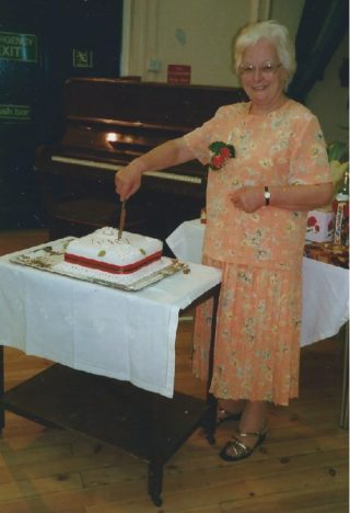 Sylvia Usher, President, Wivenhoe branch of the WI, cutting the 81 years cake in 1999