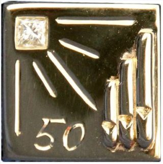 Close up of Graham Wadley's especially designed lapel pin wih its organ pipe design and diamond decoration.