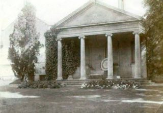 The columns and portico which were added onto the rear of the gardener's cottage. The picture shows the archery target under the portico. | Wivenhoe Memories Collection