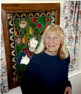 This is a picture of Anne Zemaitis Howard taken in the late 1990s standing in front of another of her stained glass panels, this one of Kane & Abel