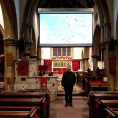Rev Erwin Lammens standing under the big screen in St Mary's on which the Wivenhoe History Group were displaying their PowerPoint presentation about the men from Wivenhoe who were killed and where their families lived. | Peter Hill