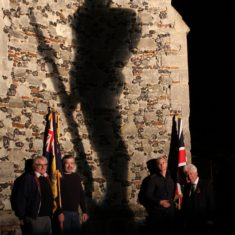 Jerry Davis, Chairman of the Wivenhoe branch of RBL with standard bearers Dan Luxford and Will Wheatley and branch President Peter Hill with the 'Tommy' silhouette made by Dave Sleightholm which had been projected on to the church tower for the ten days leading up to the 11th November commemoration. | Photo by Frances Belsham
