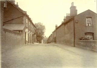 Queens Road, Wivenhoe. The Anglesea Arms in the distance [which closed in 1922]. | Mersea Museum, John Leather Collection