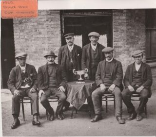 "George is the one standing with the cheese cutter hat and watch chain. The photo was taken outside the Shipwright Arms in 1922 to celebrate winning the Smack race which were fast fishing boats under sail. The wording above the door states: ""George Hillyard licensed to sell beer and tobacco"". The man on the far left is Johnny Turner 