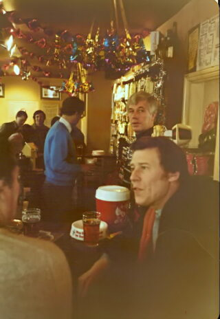 Colin Andrews (standing) in the bar of The Station pub with customers | Photo: Wivenhoe Memories Collection