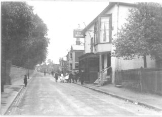 The High Street looking north. 'Circumference' Goodwin, the Attendance Officer from the National School further up the High Street, is walking to the right of the group of children. Wivenhoe Hall wall still very much in evidence. | Photo: Wivenhoe Memories Collection
